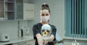 Stående av en doktor för ung kvinna med en kirurgisk maskering och handskar i det moderna klinikrummet som rymmer en stor mänskli arkivfilmer
