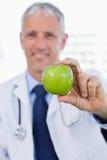 Stående av en doktor som visar ett äpple Royaltyfria Foton