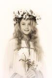 Stående av en eftertänksam flicka med en krans av blommor på hennes huvud Arkivbild