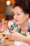 Stående av en elegant äldre dam med en förbunden hand arkivbilder
