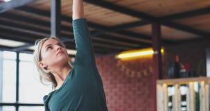 Stående av en europeisk dam med övande yogaövningar för blont hår i morgonen hemma i en modern vardagsrum på arkivfilmer
