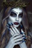 Stående av en förfärliga läskiga Corpse Bride i krans med döda blommor, halloween makeup och lång manikyr Design av Arkivbilder