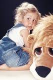 Stående av en förskräckt liten flicka i grov bomullstvilloveraller som sitter i en studio på svart bakgrund royaltyfri foto