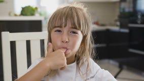 Stående av en förtjusande liten flicka som hemma äter den nya söta kakan Charmig flicka med långt hår i en vit klänning stock video