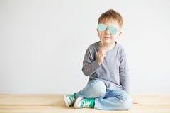 Stående av en förtjusande liten unge med exponeringsglas för blått papper Arkivfoto