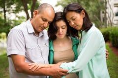 Stående av en familj som ber med deras dotter arkivfoton