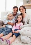 Stående av en familj som kopplar av i deras vardagsrum Arkivbilder