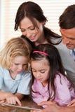 Stående av en familj som tillsammans använder en tabletdator Arkivfoto