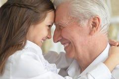 Stående av en farfar och en sondotter som har gyckel royaltyfri fotografi