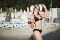 Stående av en flicka i en baddräkt på stranden arkivfoto
