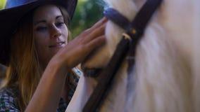 Stående av en flicka i en cowboyhatt som slår en häst stock video