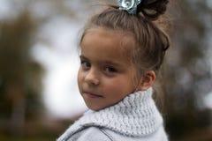Stående av en flicka i en grå kofta Arkivbild