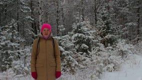 Stående av en flicka i en ljus rosa hatt i en snöig vinterskog under snöfall lager videofilmer