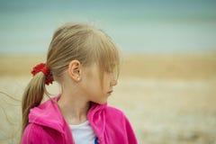 Stående av en flicka i ett kallt väder för röd dräkt på den suddiga bakgrunden av havet Arkivfoto
