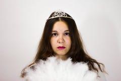 St?ende av en flicka i en krona och med en vit fan arkivbilder