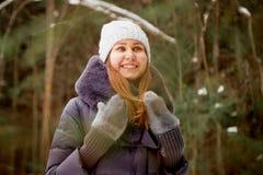 Stående av en flicka i en pinjeskog på en vinterdag royaltyfri foto