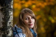 Stående av en flicka i en skog nära ett björkträd Fotografering för Bildbyråer