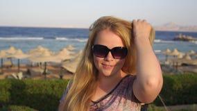 Stående av en flicka i solglasögon på stranden arkivfilmer