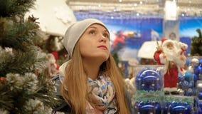 Stående av en flicka i en supermarket på bakgrunden av julpynt arkivfilmer