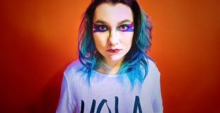 Stående av en flicka med blått hår i ett mycket färgrikt smink arkivfoto