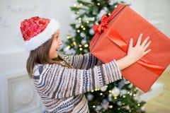 Stående av en flicka med en julklapp Arkivbild