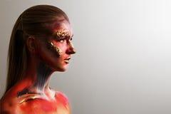 Stående av en flicka med en maskering på hans framsida makeup för halloween, grå bakgrund Arkivbilder