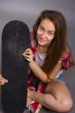 Stående av en flicka med en skateboard i studion Fotografering för Bildbyråer