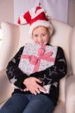 Stående av en flicka med gåvan och julhatten Arkivbild