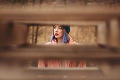 Stående av en flicka med kulört hår på naturbakgrund med några suddiga träbräden i förgrunden arkivbilder