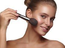 Stående av en flicka med ren och sund glödande slät hud, som applicerar daglig makeup på hennes framsida genom att använda en bor royaltyfria bilder