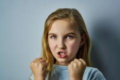 Stående av en flicka med sinnesrörelser på hennes framsida fotografering för bildbyråer