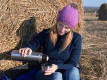 Stående av en flicka nära en höstack som häller en drink från en termosflaska Arkivfoto