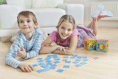 Stående av en flicka och en liten broder som ligger på golv med kort Fotografering för Bildbyråer
