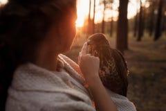 Stående av en flicka och en falkblick på de i strålarna av inställningssolen fotografering för bildbyråer