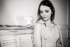 Stående av en flicka om pianot Arkivbild