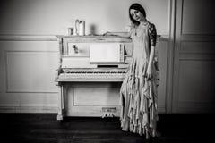 Stående av en flicka om pianot Arkivfoto
