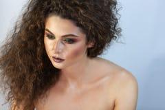 Stående av en flicka på en bakgrund med makeup arkivfoton
