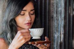 Stående av en flicka som dricker kaffe i ett tappningkafé på terrassen i Asien Sniffar, dricker Arkivbilder