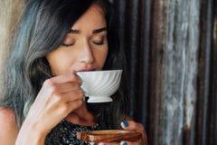 Stående av en flicka som dricker kaffe i ett tappningkafé på terrassen i Asien Sniffar, dricker Royaltyfri Foto