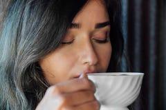 Stående av en flicka som dricker kaffe i ett tappningkafé på terrassen i Asien Sniffar, dricker Arkivbild