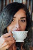 Stående av en flicka som dricker kaffe i ett tappningkafé på terrassen i Asien Sniffar, dricker Royaltyfria Foton