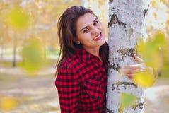 stående av en flicka som kramar en björk försiktigt handlag av händerna till trädet arkivfoton