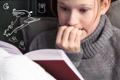Stående av en flicka som läser den mycket intressanta läskiga boken arkivbilder