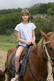 Stående av en flicka som rider en brun häst naturen går arkivfoton