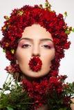 Stående av en flicka som täckas i lösa blommor Arkivbild