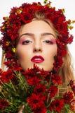 Stående av en flicka som täckas i lösa blommor Arkivbilder