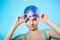 Stående av en flickaidrottskvinna i en badmössa och exponeringsglas Flickan bär dykningskyddsglasögon En ljus blå bakgrund Royaltyfria Bilder