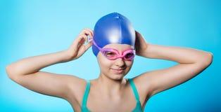 Stående av en flickaidrottskvinna i en badmössa och exponeringsglas Flickan bär dykningskyddsglasögon En ljus blå bakgrund Arkivbild