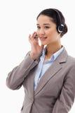 Stående av en fokuserad operatör som poserar med en hörlurar med mikrofon Arkivfoton
