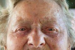 Stående av en framsida för gammal kvinna med skrynklor och ögon som är fulla av revor royaltyfri fotografi